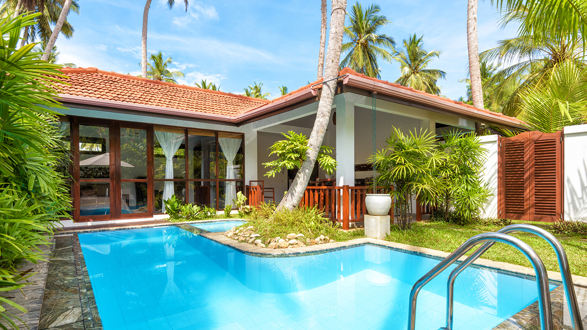 Luxury, small residential home with a swimming pool, surrounded by palm trees, photographed during a home inspection